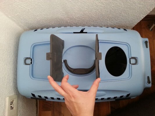 Two flaps on top of a cat carrier.